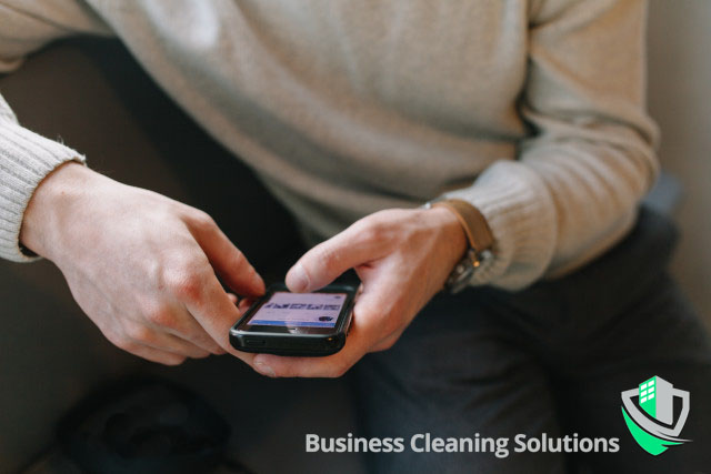 Man with cell phone working from home calls BCS for a free consultation because clean equals safe