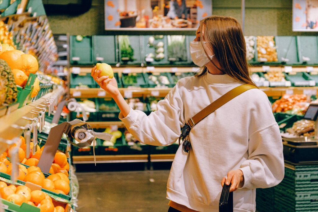Woman shopping while wearing a mask for health and safety during the Covid-19 pandemic.