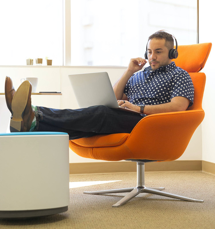 A man works on his laptop at the office while sitting on an upholstered computer chair.