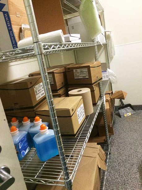 Clean and organized janitorial closet with shelving and room to walk.