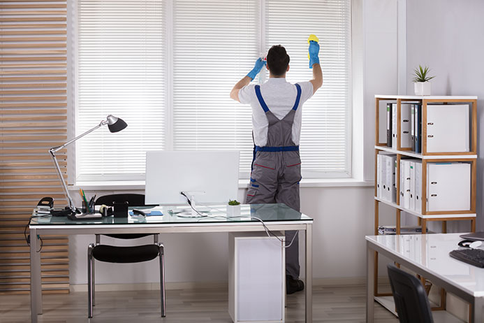 Professional janitor cleans office window blinds.