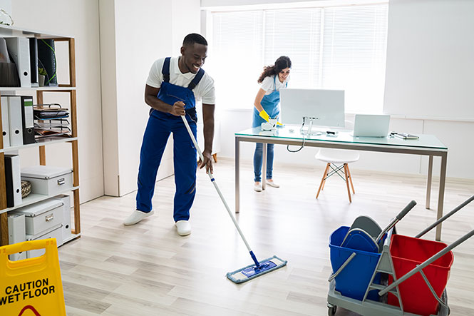 male janitor mopping a commercial office.
