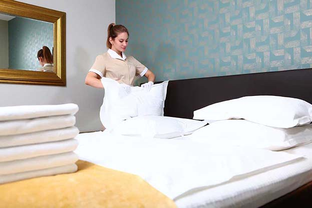 Hotel Housekeeper changes bedsheets and linens.