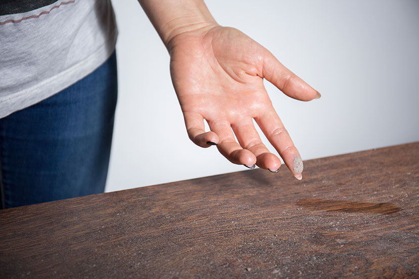 A woman wipes finger through a dusty desk.
