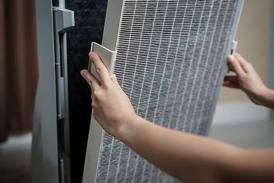 A woman changes a dirty HVAC air filter.