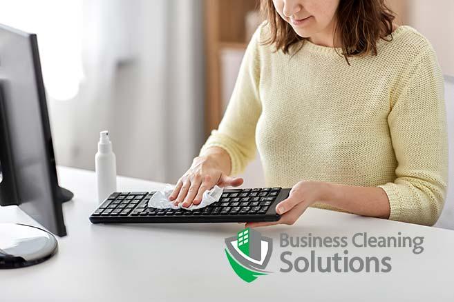 Woman sanitizes her office keyboard