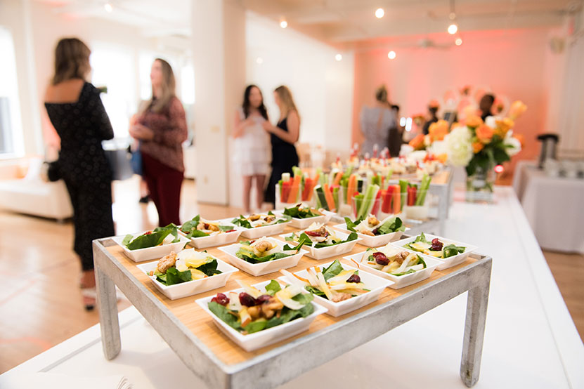 An office party with tables full of catered food.