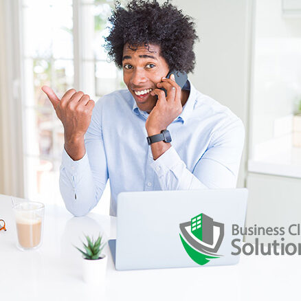 Man smiles while on the phone giving feedback to his commercial cleaning company.