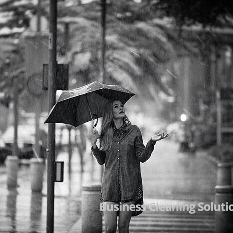 A woman caught in the rain with umbrella